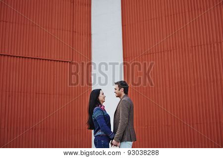 Young couple in casualwear looking at one another by wall