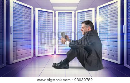 Mature businessman sitting using tablet against digitally generated server room with towers