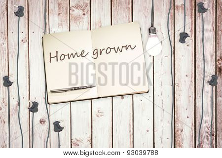 The word home grown against notepad and plugs on wooden background