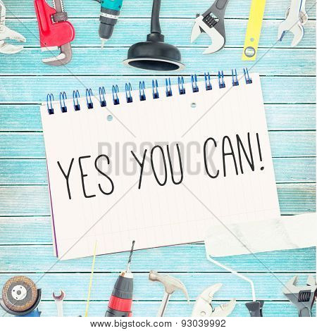 The word yes you can! against tools and notepad on wooden background