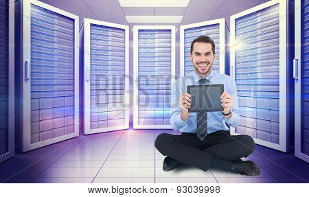 Smiling businessman showing his digital tablet against digitally generated server room with towers