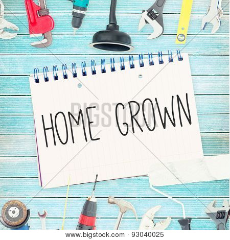 The word home grown against tools and notepad on wooden background