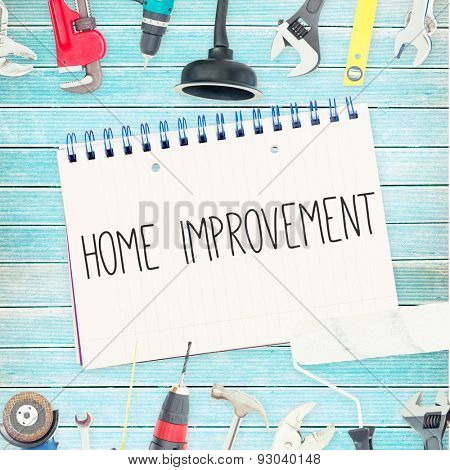 The word home improvement against tools and notepad on wooden background