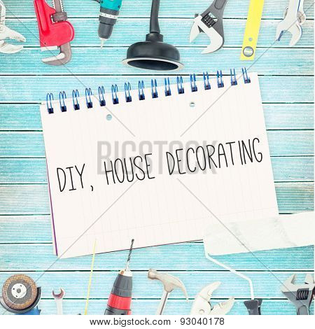 The word diy, house decorating against tools and notepad on wooden background