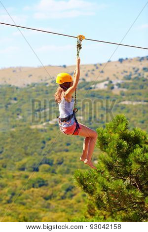 Young Woman Flying Down On Zipline In Mountain, Extreme Sport