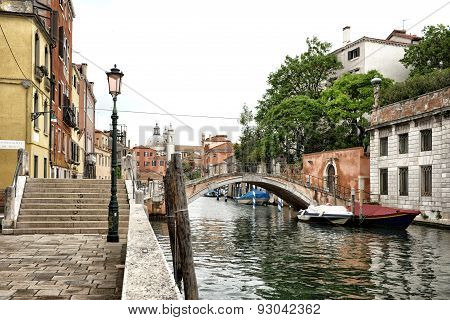 Foot Bridge Spanning Venetian Canal In Urban Area