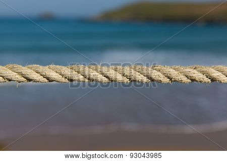Length of rope pulled tight against a blurred background of sea waves and coast