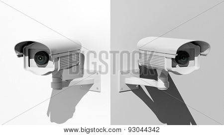 Two security surveillance cameras on white wall corner