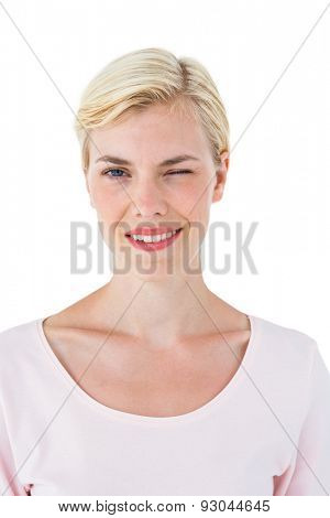 Attractive blonde woman winking on white background