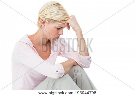 Depressed blonde woman sitting on the floor on white background