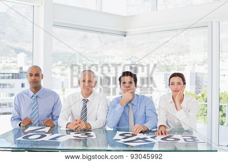 Concentrated business team sitting with their vote on the desk in the office