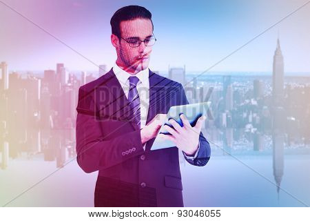Unsmiling businessman using tablet pc against skyscraper