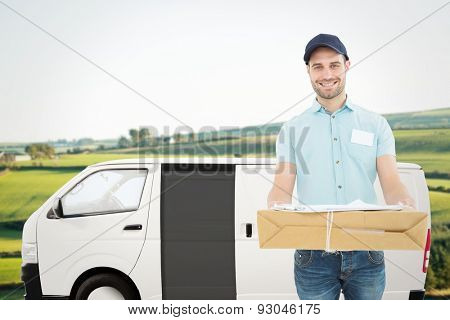 Handsome courier man with parcel against scenic landscape