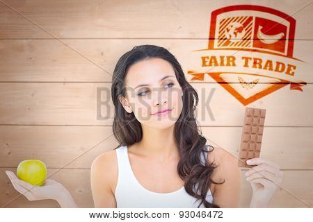Pretty brunette deciding between apple and chocolate against overhead of wooden planks