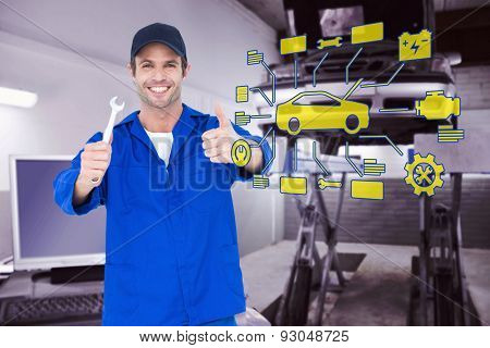 Happy mechanic holding spanner against auto repair shop
