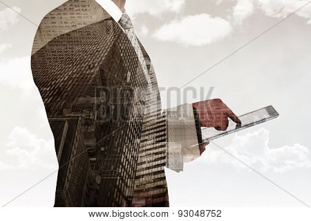 Businessman using his tablet pc against low angle view of skyscrapers