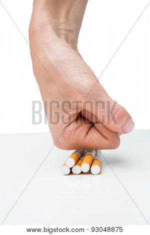 Hand squashing batch of cigarettes on white background