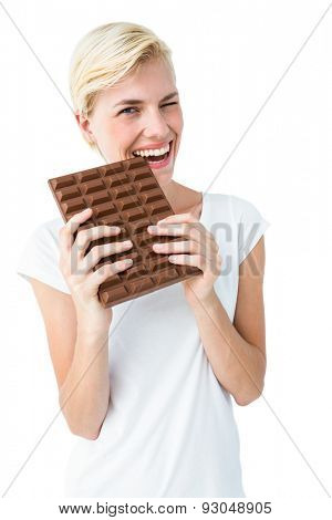 Attractive woman biting bar of chocolate on white background