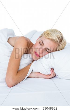 Smiling blonde woman napping in her bed on white background