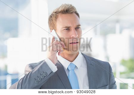 Thoughtful businessman calling on the phone in the office