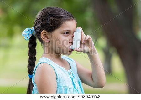 Little girl using his inhaler on a sunny day