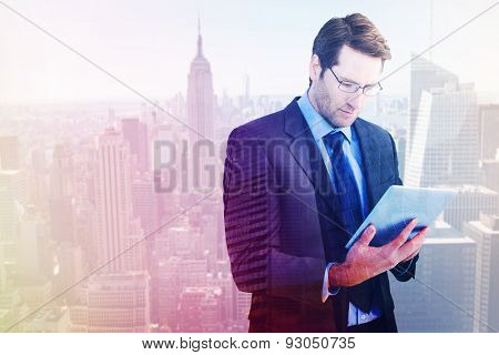 Businessman using a tablet computer against low angle view of skyscrapers at sunset