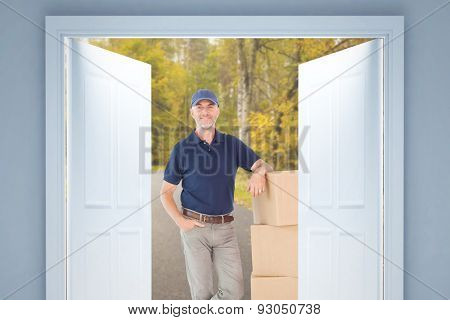 Happy delivery man leaning on pile of cardboard boxes against country road along trees in the lush forest