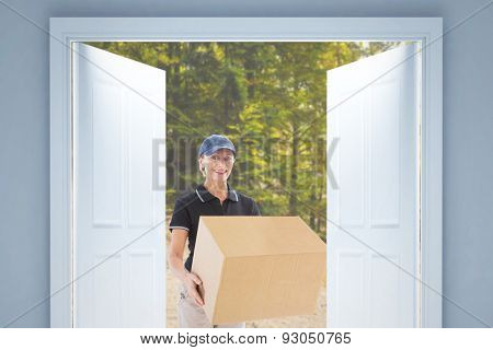 Happy delivery woman holding cardboard box against tarmac curved country road in forest