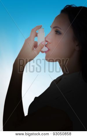 Asthmatic brunette using her inhaler against blue sky