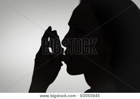 Asthmatic brunette using her inhaler against grey vignette