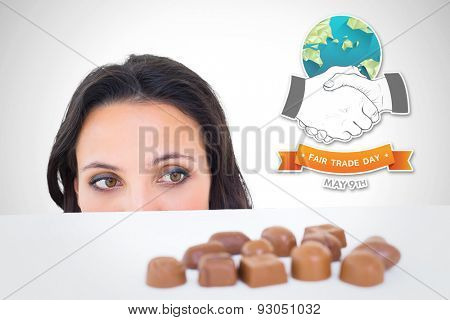 Pretty brunette peeking at chocolate against white background with vignette