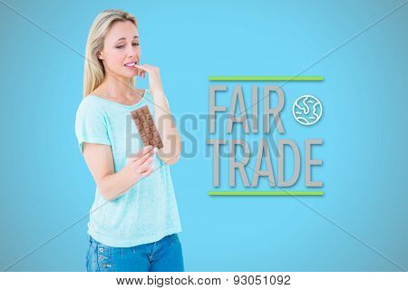 Pretty blonde feeling guilty to eat bar of chocolate against blue background with vignette