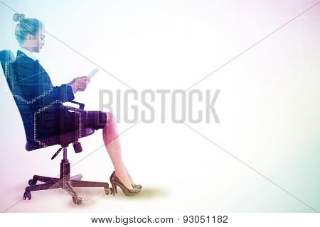 Businesswoman sitting on swivel chair with tablet against server room with towers