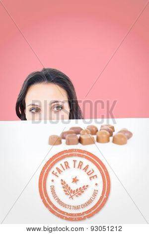 Pretty brunette peeking at chocolate against red background