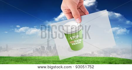 Hand showing card against blue sky over city