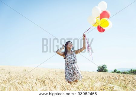 Woman With Balloons In A Wheat Field