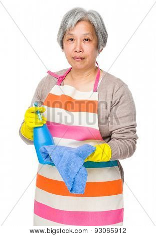 Asian old housewife with rag and bottle spray