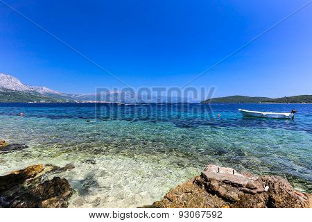 blue beach at Korcula Croatia with boat and swimmers