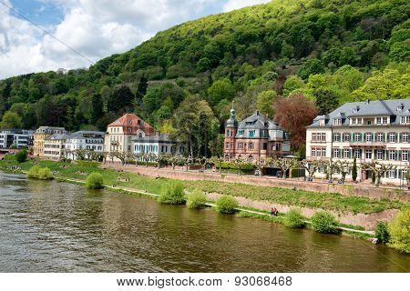 Historic buildings on the bank of the Neckar River in Heidelberg, Germany on the slopes of a forested hill