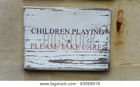 Children Playing - Please Take Care rustic wooden signboard with peeling paint mounted on a wall warning of children in the vicinity