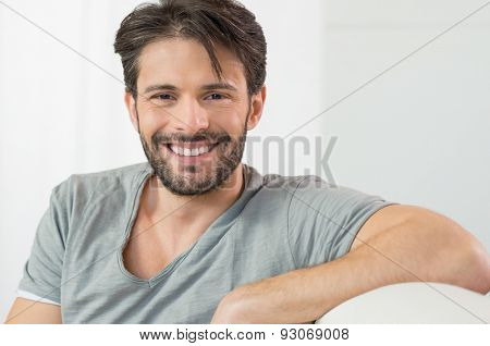 Portrait of smiling man looking at camera sitting on couch
