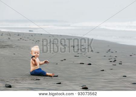 Child Sitting Alone On Black Sand Sea Beach