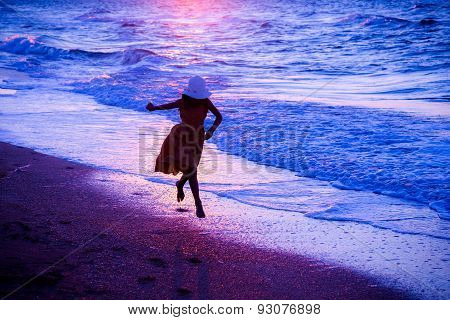 Girl running along the surf