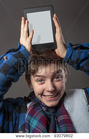 Smiling Mad Boy Holding A Tablet Computer On His Head