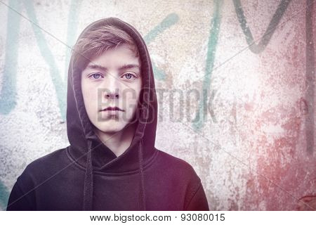 Portrait Of A Teenage Boy With Black Hoodie In Front Of A Graffiti