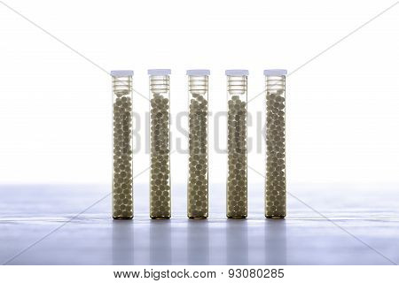 Five Small Glass Tubes With Homeopathy Globules, White Background