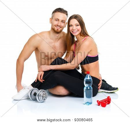 Athletic Couple - Man And Woman After Fitness Exercise With Dumbbells And Bottle Of Water Sitting On