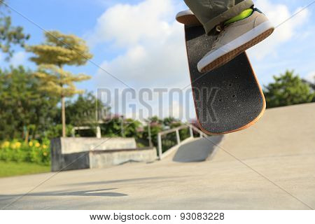 skateboarder legs doing a ollie trick at skatepark