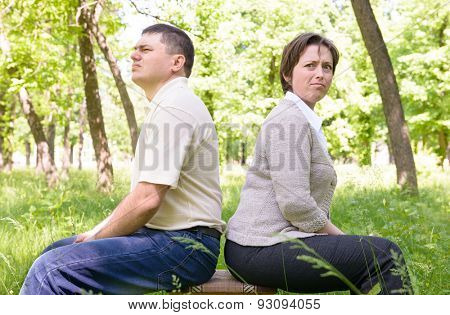 Unhappy couple in green summer park