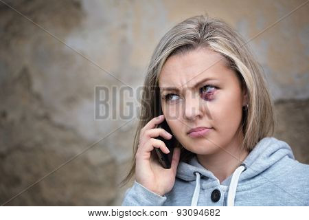 Scared woman with bruise on face calling to get help
